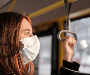 woman on public transport with a face mask on covid-19